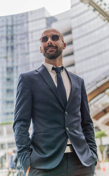 Low Angle View Of Smiling Businessman Wearing Sunglasses While Standing In City