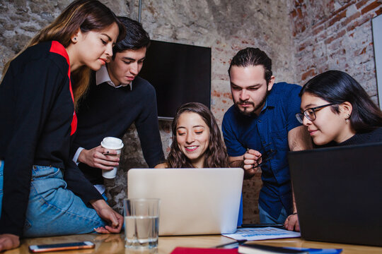Young latin woman working with computer and her coworkers at the office or coworking in Mexico or South America, Mexican teamwork