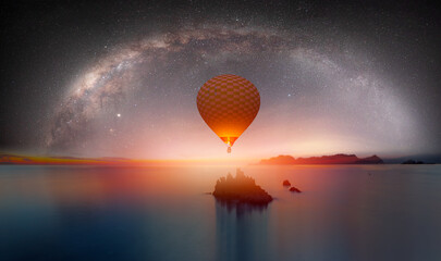 Wall Mural - The milky way galaxy over the sea and  silhouette of rock in the night sky - Hot air balloon flying over night sea