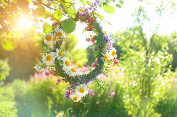 Meadow flower wreath.. summer flower wreath in garden, sunny day. Farm lifestyle. Summer Solstice Day, Midsummer. floral traditional decor