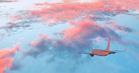 Passenger airplane flying above amazing clouds during sunset  - Airplane in the sky at sunset