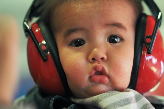 Close-up Portrait Of Cute Baby Boy Wearing Headphones