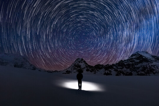 Circular Star trails facing north with Polaris the north star in centre and a silhouette human watching the stars move