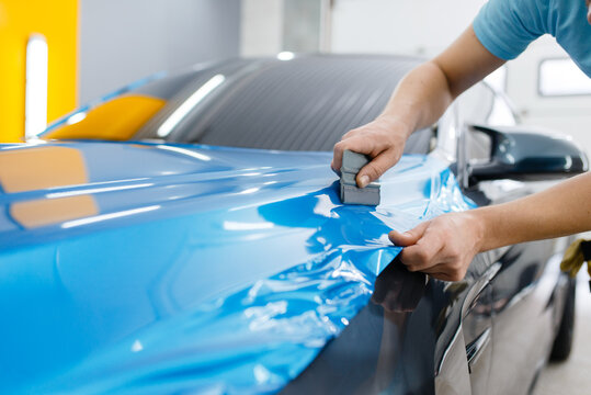 Car wrapping, mechanic with squeegee installs film