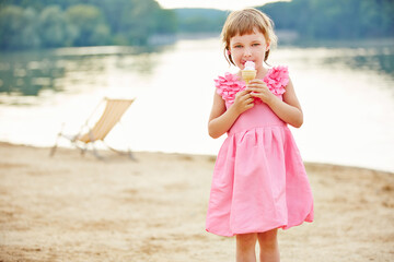 Portrait Of Cute Girl Eating Ice Cream Cone While Standing At Beach