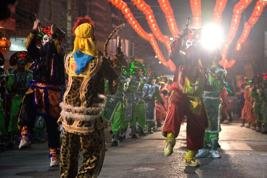 People Wearing Costumes Dancing On Street During Event At Night