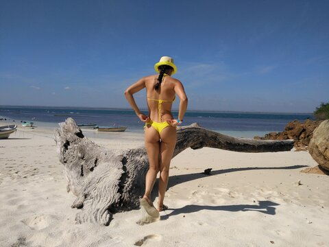 Rear View Of Mid Adult Woman In Yellow Bikini Walking At Beach Against Blue Sky During Sunny Day