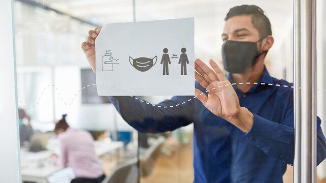 Business Mann befestigt Aushang mit Hygieneregeln im Büro