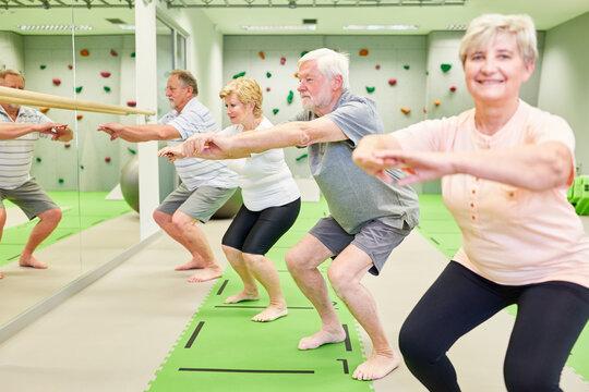 Group of vital seniors doing squats