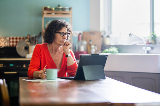 Beautiful middle-aged woman sitting in her kitchen, working on her laptop while drinking tea.
