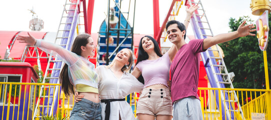 Group of happy best friends laughing and having fun at amusement park, holiday travel with friends concept