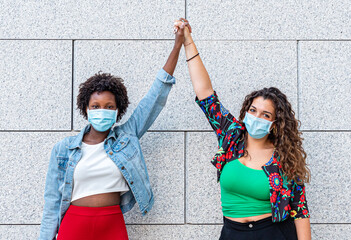 two young women friends, one white and one black, raise their fists together as a sign of sisterhood and protest against racism, new socialization with protective masks