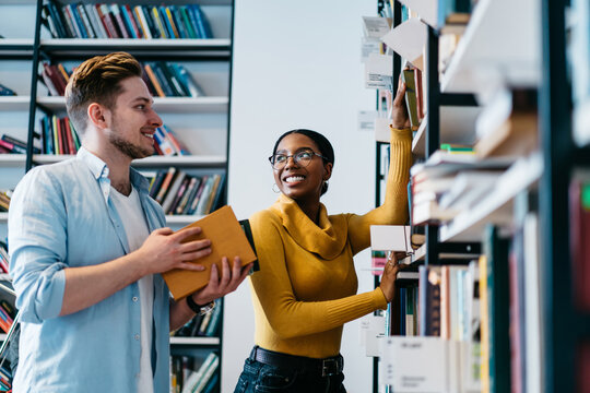 Positive two multicultural young people teamworking in library.Cheerful diverse hipster students dressed in formal wear pulling books from shelf choosing literature for writing course work