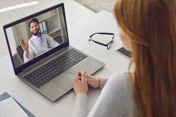 Online doctor consultation. Male doctor waving a hand from a laptop monitor video consultation for...