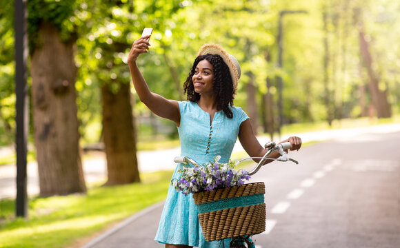 Pretty black girl with bike taking selfie on smartphone at beautiful summer park