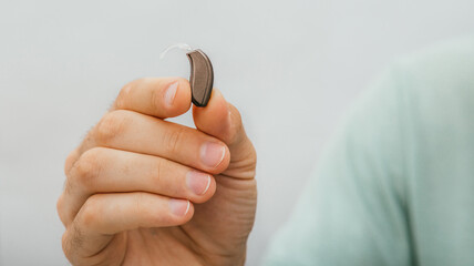 BTE hearing aid close-up in a male hand. Hearing solution, man holds a hearing aid, macro