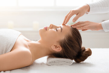Acupressure head massage for young woman at spa