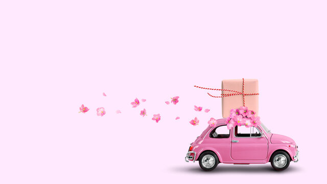 Pink car with gift box on a roof with flowers on pink background.