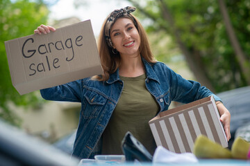 Pretty young woman holding a garage sale sign