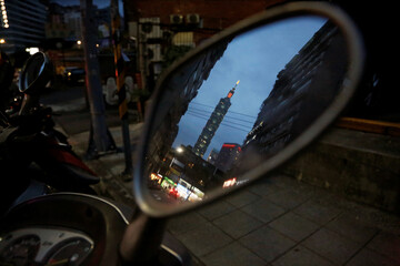 Reflection of Taipei 101 is reflected in the rear mirror of a motorbike, in Taipei