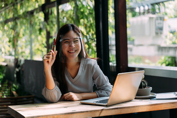 Young 20s Asian woman looking at camera while wearing a protective mask with laptop, mobile phone,...