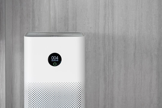 Indoor air purifier with digital monitor screen in living room, show air quality in the room and air pollution levels in the room. with wood laminate wall background