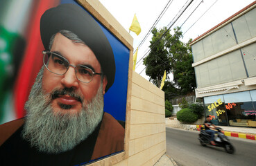 A man rides a motorbike past a picture of Lebanon's Hezbollah leader Sayyed Hassan Nasrallah, near Sidon