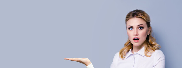 Portrait image of excited surprised blond businesswoman with opened mouth, showing something or copy space area for some imaginary, slogan or text. Success in business concept. Grey color background.