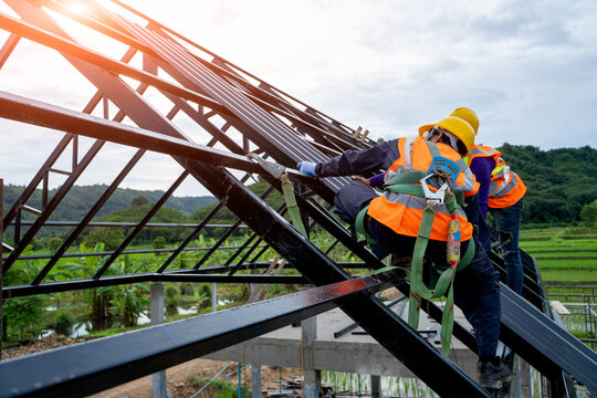 Construction worker wearing safety harness using secondary safet