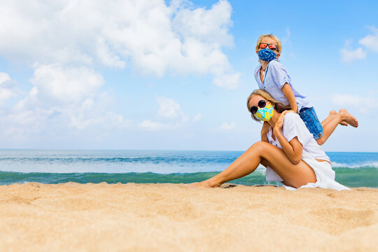 Mother, child in face masks have fun on sea beach