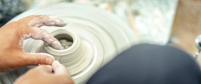 koreanischer Meister dreht an der elektrischen Drehscheibe eine zentrische Halterung aus feuchter Keramikmasse um anschließend getrocknete kleine Espresso Tassen darauf zu fixieren und abzudrehen