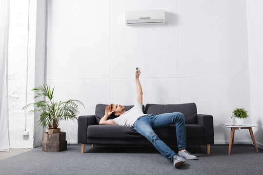 exhausted man holding remote controller and suffering from heat with broken air conditioner at home