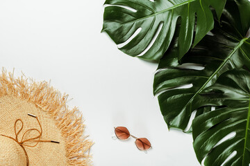 top view of green palm leaves, straw hat and sunglasses on white background