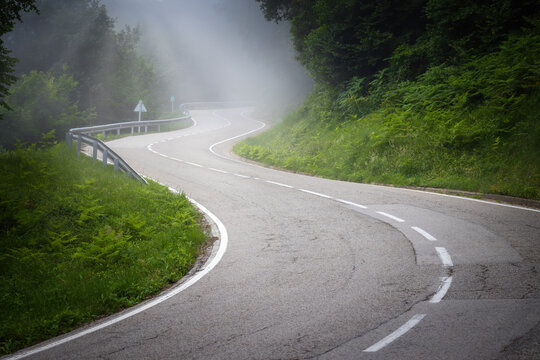 Empty curved road in a foggy day