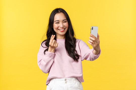 People emotions, lifestyle leisure and beauty concept. Cheerful asian girl over yellow background taking selfie on mobile phone, use photo filters app and show heart gesture