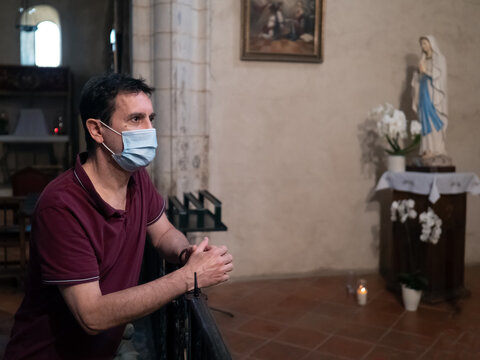 An anxious man wearing a surgical mask in a church