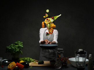 Beautiful mature woman cooking vegetable salad in the kitchen, tosses vegetables from the pan....