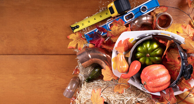 Happy Thanksgiving with construction tools, maple leaves and pumpkin on wood background. Autumn composition with copy space. Plumber Thanksgiving. Top view.