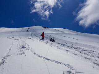 Fototapeta Low Angle View Of Friends On Snowcapped Mountain Against Blue Sky