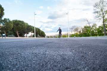 Fotomurales - Surface Level Of Young Man Skating On Road Against Cloudy Sky