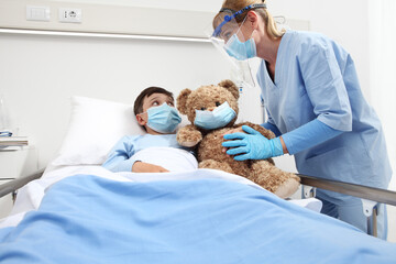 nurse takes care of the patient child in hospital bed playing with teddy bear, wearing protective masks, corona virus covid 19 protection concept,
