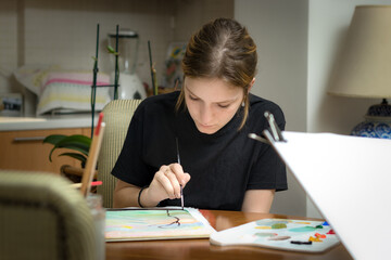 A teenage woman painting on paper with acrylic holding a painbrush sitting at home.
