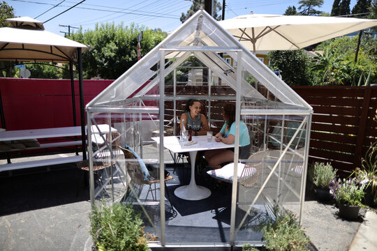 People eat lunch in a social distancing greenhouse dining pod amid the outbreak of the coronavirus disease (COVID-19) in Los Angeles