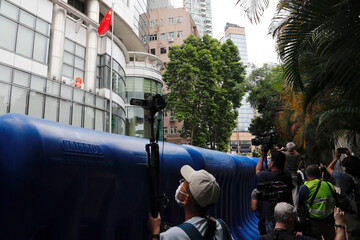 A journalist takes video through water filled barriers after the opening ceremony of a temporary national security office, in Hong Kong