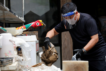 A man wearing face mask and face shield to prevent coronavirus disease (COVID-19) infection, cleans up his father's house after floods caused by torrential rain in Hitoyoshi, Kumamoto Prefecture