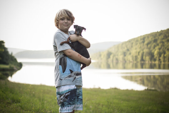 Portrait Of Smiling Boy With Puppy Standing On Grass Against Lake And Sky
