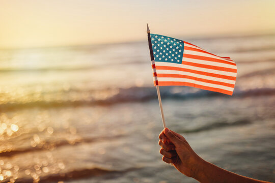 Close-up Of Hand Holding American Flag Against Sea During Sunset