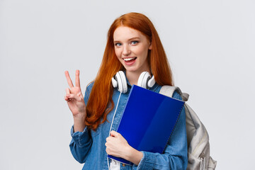 Lovely friendly college student, redhead girl with papers, documents for school, holding backpack and wear headphones over neck, make peace gesture informal greeting classmate, white background