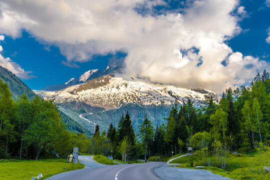 Road By Trees On Snowcapped Mountains Against Sky