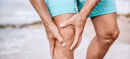 Knee pain sport injury from running exercise. Man runner holding painful knees, hurting from sprain joint or arthritis. Closeup of leg panoramic. Jogging sport.